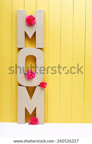 MOM text letters with pink carnations on yellow wooden background - stock photo