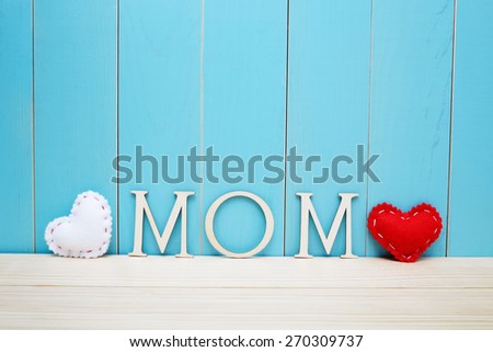 MOM text letters with white and red hearts over blue wooden background - stock photo