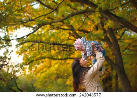 Mom throws baby. lilac bloom, mother and child communication, joy, happiness, emotion, autumn - stock photo