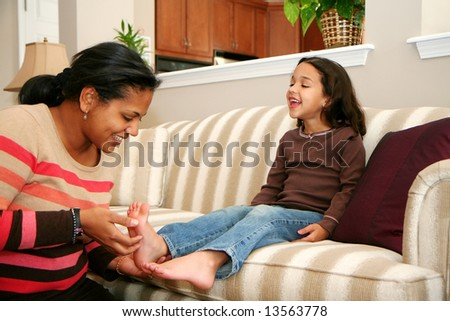 Mom tickles her daughter while on the couch - stock photo