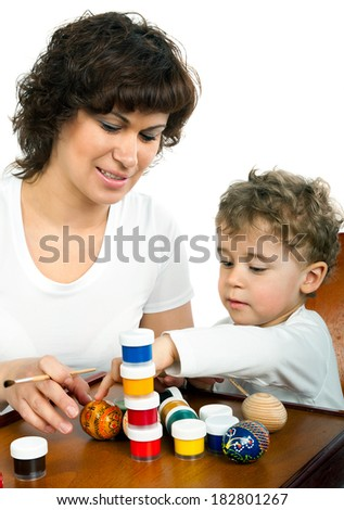 Mom whith baby paint Easter eggs on white - stock photo