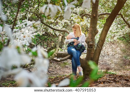 Mom with baby boy sitting on tree branch in the flowered spring garden - stock photo