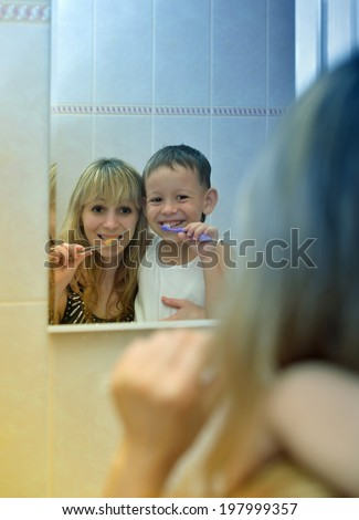 Mom with boy standing before a mirror and brush their teeth - stock photo