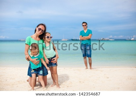 Mom with her cute daughters in the foreground and dad in the background on the beach - stock photo