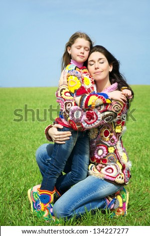 Mom with her daughter on a green field - stock photo