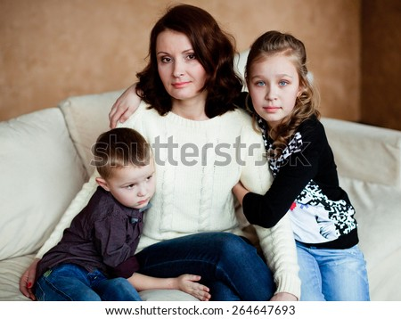 Mom with her two children sitting on the couch at home - stock photo