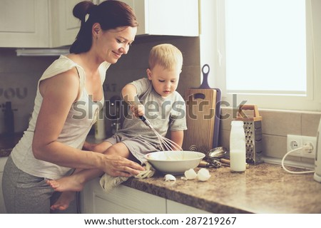 Mom with her 2 years old child cooking holiday pie in the kitchen to Mothers day, casual lifestyle photo series in real life interior - stock photo