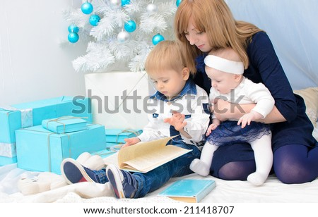Mom with kids in New Year's interior in turquoise and white colors - stock photo
