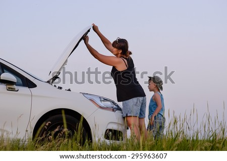 Mom with Son Looking at the Camera While Opening the Front of a Defective Car at the Grassy Ground. - stock photo