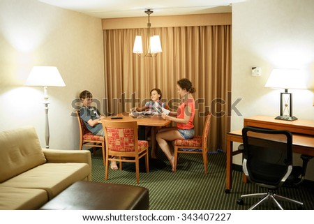 Mom with two kids read magazines at the table - stock photo