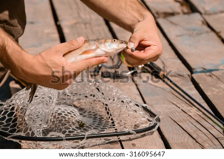 Moment of happiness. Close up of hands of professional fisherman getting fish from the rod while fishing - stock photo