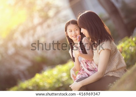 Moment of tenderness, Happy young mother with her daughter at park - stock photo