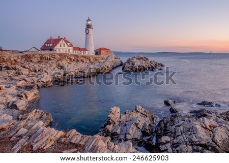 Moments before the sun rises a soft pink light is cast across the Portland Head Lighthouse and the rocks - stock photo