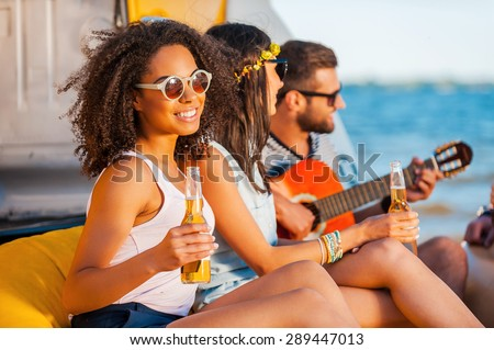 Moments of happiness. Happy young African woman holding beer and smiling while sitting together with her friends on the beach  - stock photo