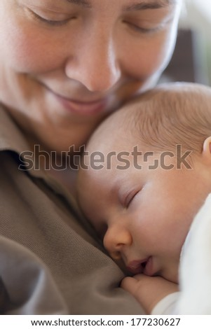 Moments of harmony and tenderness: Happy smiling mother holding her peaceful baby boy while he's sleeping on her chest. - stock photo