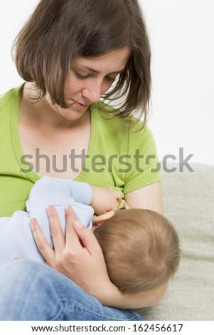 Moments of tenderness and care: Mother nursing her baby boy. - stock photo