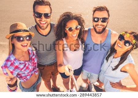 Moments worth remembering. Top view of group of cheerful young people making selfie while standing outdoors together - stock photo