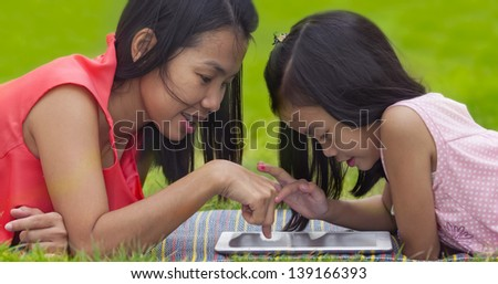 Mon and baby take tablet on the green nature. - stock photo