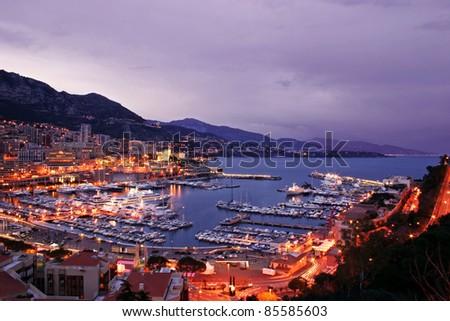 Monaco scenic at night including lavish yachts and the Monte Carlo skyline - stock photo