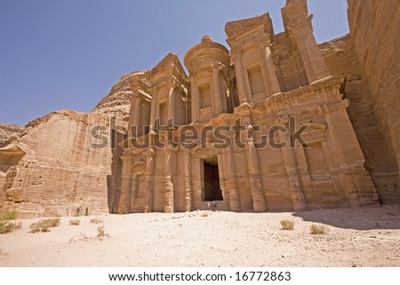 Monastery with people shown to scale Petra Jordan - stock photo