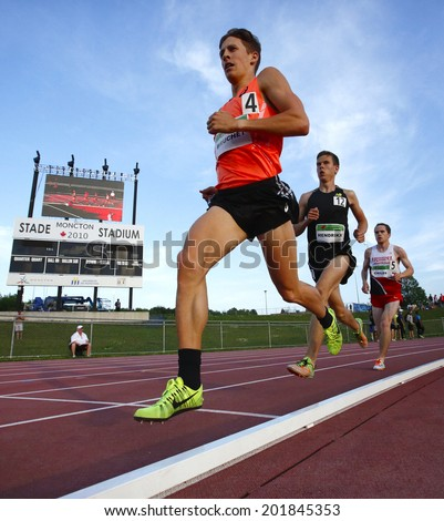 MONCTON, CANADA - June 28: Lucas Bruchet is followed by Aaron Hendrikx and Clifford Childs in the 5000-metre championship at the Canadian Track & Field Championships June 28, 2014 in Moncton, Canada. - stock photo
