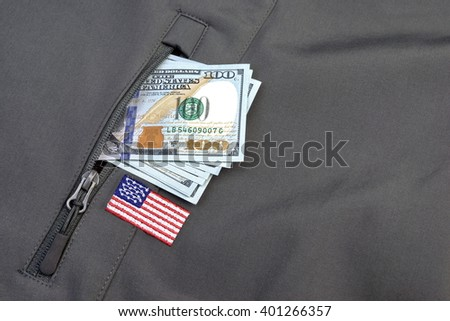Money American Dollar Pile Stuck Out Of Military Khaki Coat or Bag Pocket With American Flag Patch, Soldier Salary or Insurance or Mercenary Concept, Closeup - stock photo