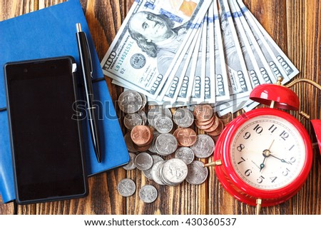 Money american hundred dollar bills, coins, phone, pen, notebook and clock closeup on wooden background. Time is money concept. Business Finance and Money concept,Save money for prepare in the future. - stock photo