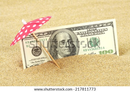 Money american hundred dollar bills in the beach sand under red and white dots sunshade  - stock photo