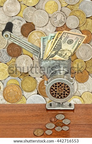 Money and business concept.Dollar banknotes in meat grinder and coins on table on lot of different coins background. - stock photo