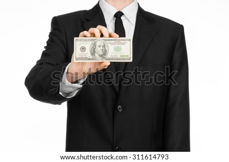 Money and business theme: a man in a black suit holding a bill of 100 dollars and features a hand gesture on an isolated white background in studio - stock photo