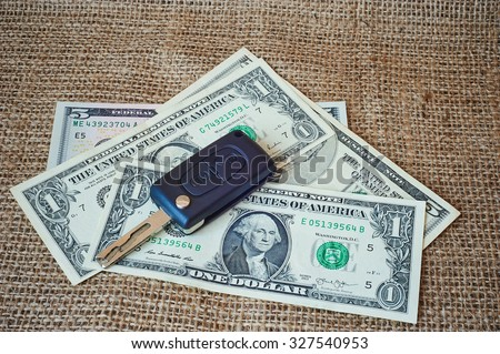 Money and car keys on a burlap background. - stock photo