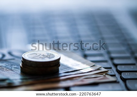 Money and coins on keyboard of computer. Online banking. Euro banknotes. - stock photo