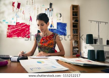 Money and financial planning, young hispanic self-employed woman checking bills and doing budget with calculator, computer and papers in fashion design studio - stock photo
