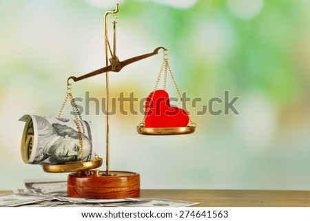 Money and heart in balance scales on light blurred background - stock photo