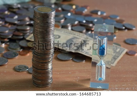 Money and hourglass on the table - stock photo