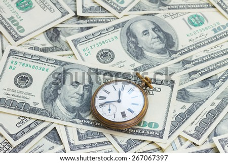 money and time concept - old pocket watch on pile of american 100 bill dollars - stock photo