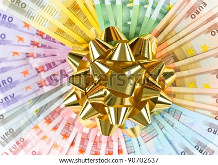 money as a gift. golden ribbon on euro banknotes background - stock photo