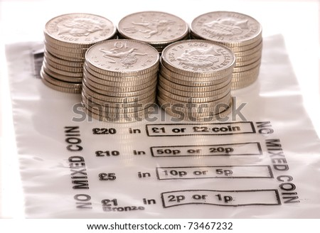 Money bag with sterling ten pence coins studio - stock photo