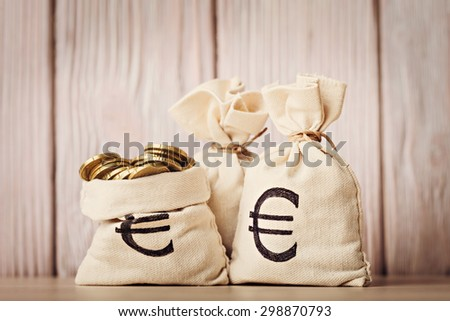 Money bags with euro coins over defocused wooden background - stock photo