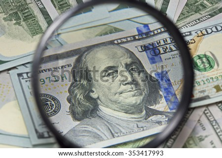 Money Banknotes through a magnifying glass. Business, financial success and making money concept: new 100 US dollar banknotes. Stack of hundred US Dollar bills. Macro. Finance background. - stock photo