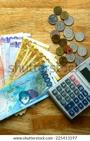 Money Bills on a table and a calculator Photo of Money Bills and a calculator on top of a wooden table - stock photo