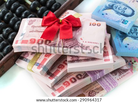 Money bonus money with red bow and abacus  - stock photo