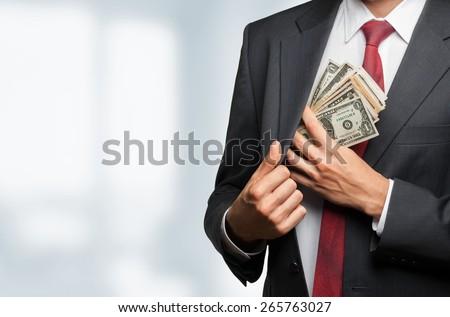Money. Business man hiding money in pocket on black background - stock photo