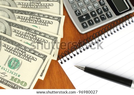 Money, calculator, notepad and pen on wooden background - stock photo