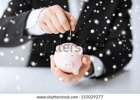 money, cash, finances, savings, banking concept - man putting coin into small piggy bank - stock photo