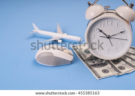 money, clock, airplane model  and computer mouse on blue background, Balance working concept. - stock photo