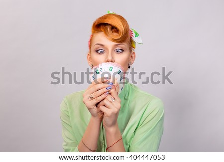 Money. Closeup red head beautiful young woman pretty excited amazed greedy pinup girl green button shirt euro cash looking at currency, retro vintage 50's hairstyle isolated grey white background wall - stock photo