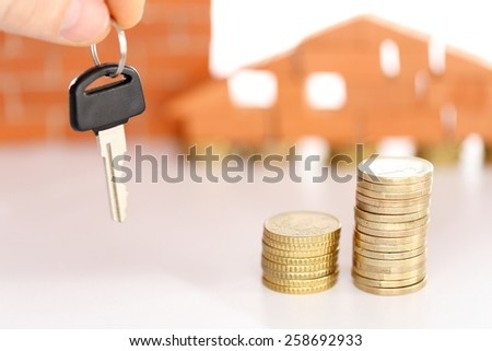 money coins and key with house in background - stock photo