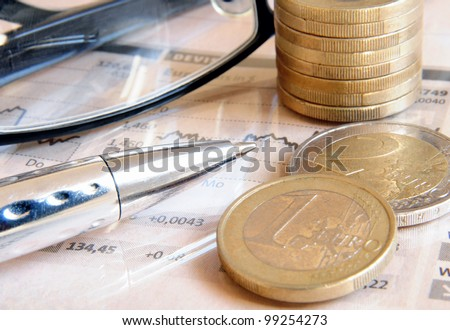 Money coins, glasses and ball pen on top of a light pink colored stock market report - stock photo