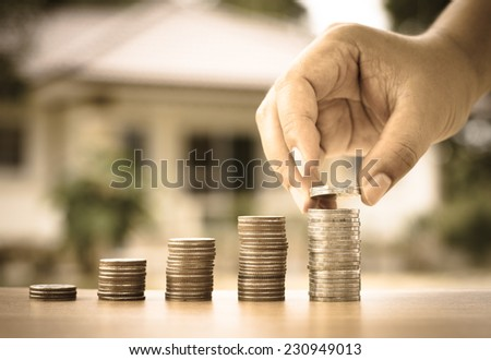 Money concept,Male hand putting money coins stack like growing graph with home, Saving for buy home concept - stock photo